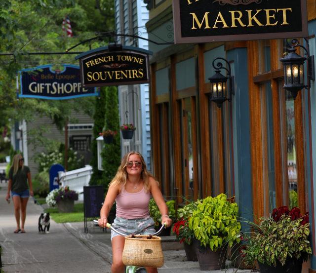 girl riding bike through village